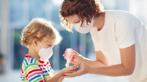 Mother and child wearing facemasks and using hand sanitizer while out in public during COVID-19 pandemic.