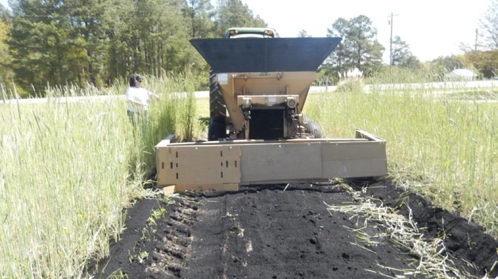A tractor spreads biochar in a field.
